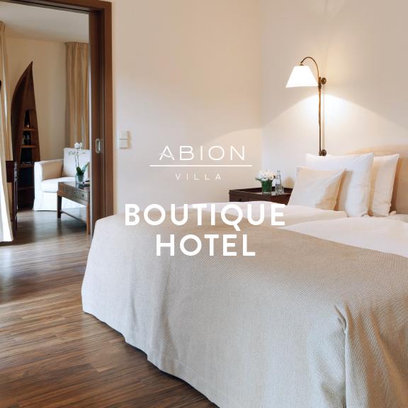"""Foto: Hotelsuite der ABION Villa, Blick auf das Kingsize-Bett und den Durchgang in den Wohnbereich - Logo der ABION Villa und Aufschrift """"BOUTIQUE HOTEL"""""""