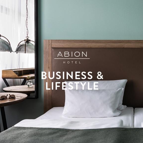 """Foto: Hotelzimmer, Ausschnitt Bett und Holzmöbel - Logo ABION Hotel und Aufschrift """"BUSINESS & LIFESTYLE"""""""