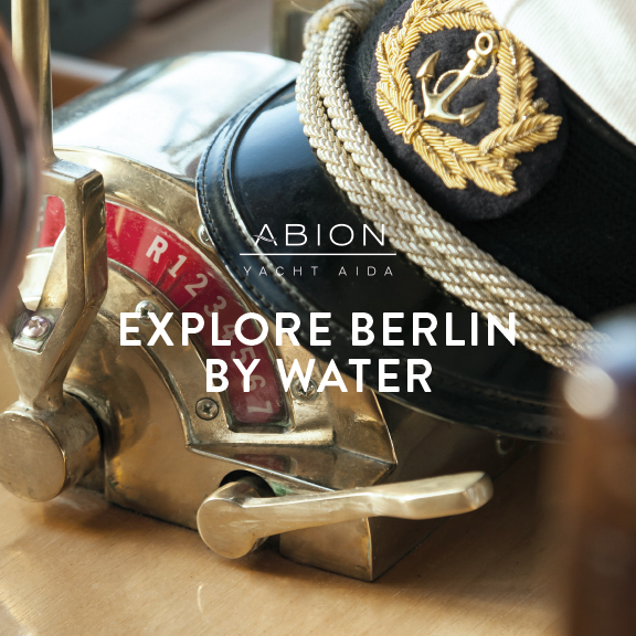 """Foto : Yacht AIDA, goldener Steuerhebel und Capitainsmütze; Abion Yacht AIDA Logo und Aufschrift """"EXPLORE BERLIN BY WATER"""""""