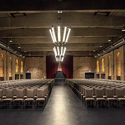 Teaser Eventlocation / BOLLES Festsäle - Foto: große Backstein-Halle mit beleuteten Bögen und hunderten Stühlen