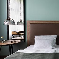 Teaser AMERON Hotel ABION - Foto: Hotelzimmer - Bett und Beistelltisch