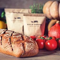 Teaser BOLLE'S KÖCHE - Foto: Frisches Brot, Tomaten, Papiertüten mit Logo Granatapfen uvm.